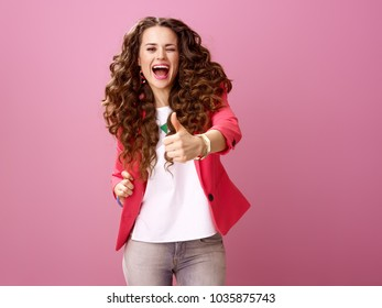 Pink Mood. Portrait of happy stylish woman with long wavy brunette hair isolated on pink showing thumbs up