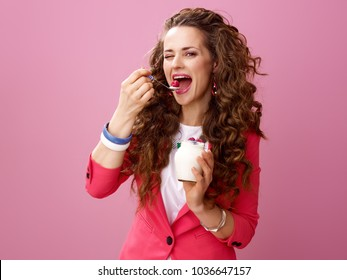 Pink Mood. Portrait of happy young woman with long wavy brunette hair isolated on pink eating farm organic yogurt