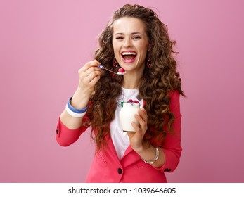 Pink Mood. Portrait of smiling stylish woman with long wavy brunette hair isolated on pink background eating farm organic yogurt