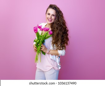 Pink Mood. Portrait of smiling trendy woman with long wavy brunette hair on pink background with a bouquet of tulips