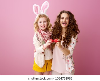 Pink Mood. smiling modern mother and daughter with wavy hair  red Easter eggs tapping isolated on pink