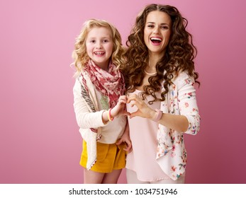 Pink Mood. smiling stylish mother and daughter with wavy hair isolated on pink background showing heart shaped hands