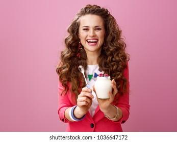 Pink Mood. smiling stylish woman with long wavy brunette hair isolated on pink background showing farm organic yogurt and spoon