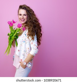 Pink Mood. smiling trendy woman with long wavy brunette hair on pink background with a bouquet of flowers