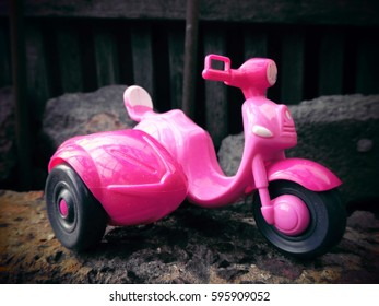 A pink motorcycle. A toy.