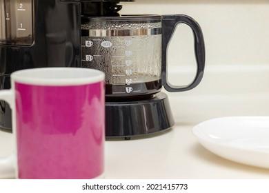 Pink mug and black coffee maker