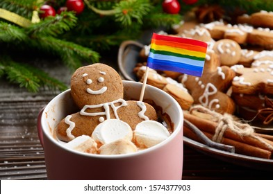 Pink mug with hot chocolate marshmallows and gingerbread man with rainbow flag on background of spruce branch and tray with cookies