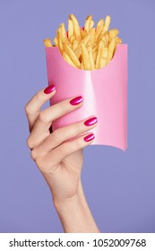 Pink Nails. Female Hands And Fries On Violet Background. Close Up Of Female With Colorful Manicure On Hands Holding Pink French Fries. Nail Art. High Quality Image.