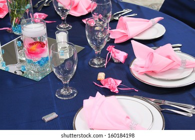 Pink napkins and white dishes on a table, ready for guests