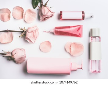 Pink natural cosmetic products with roses essential oil : gel, lotion, serum and toner roses water bottles and tubes with branding mock up on white desk background with flowers and petals, top view