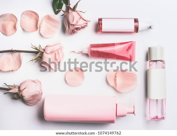 バラの精油を含むピンクの天然化粧品:白いデスクの背景に花と花びらを持つブランドとゲル、ローション、血清、トナーのバラと水のボトルとチューブ