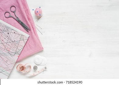 Pink natural fabric and sewing tools on  the white wooden table