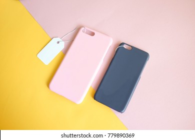 Pink and navy color plastic cover for mobile phone with price tag on colorful yellow and pink background, copy space, sale space for your branding design, corporate identity