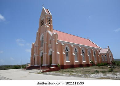 Pink Neo-Gothic architectural style church with beautiful facade Sint Willibrordus on the island of Curacao blue sky in the background