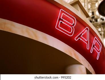 A pink neon sign above a bar