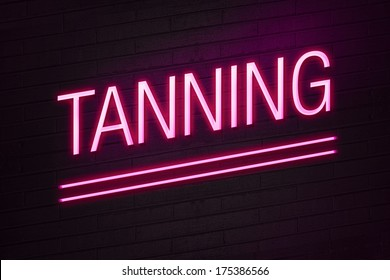 Pink neon sign with tanning text on wall