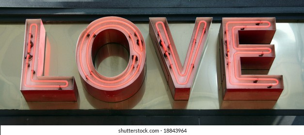 A pink neon sign that reads Love