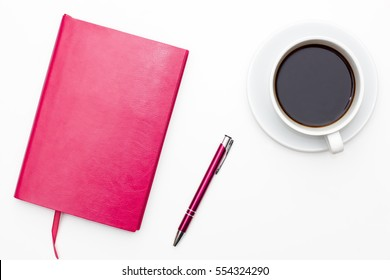 pink notebook with pen and a Cup of black coffee on white background. business minimal concept for women. Flat lay, top view.