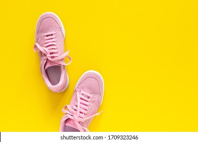 Pink nubuck sneakers isolated on a yellow background, seasonal shoes for walking and sports, top view