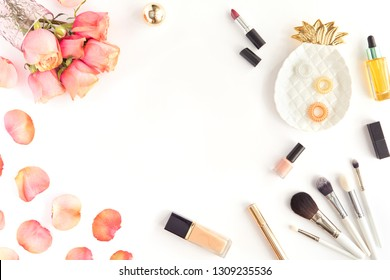 Pink office table with flowers, make up brush and cosmetics. Woman's accessories, copyspace concept. Top view, flat lay, isolated on white background, space for text.