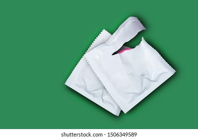 Pink opened condom and condom in pack on a Sea green background. Safe sex and reproductive health concept.
