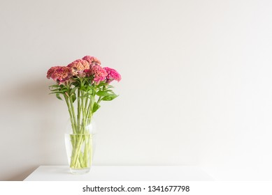 Pink and orange cockscomb flowers in glass vase on white table against neutral wall background