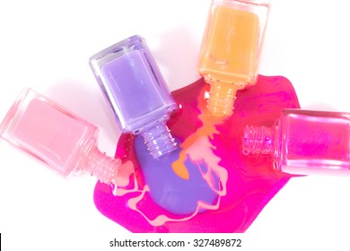 Pink, orange and purple nail polishes on the white background