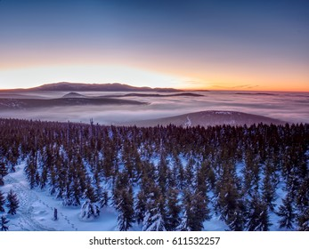 Pink orange sun rise above misty winter mountains, shinning fog.  Peaks of  mountains above creamy mist in valley.