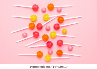 Pink, orange and yellow sweet candy lolipop on a pastel pink background