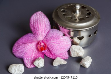 Pink orchid flower, pewter box and stones as decoration for a spa