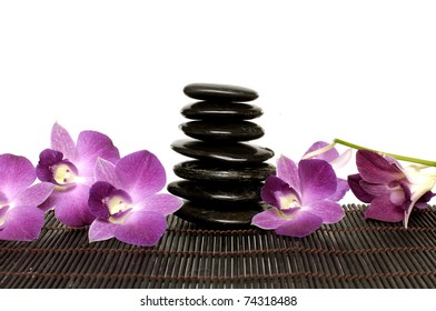 Pink orchid laying on zen stones on mat