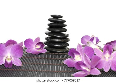 Pink orchid on stacked black stones on mat