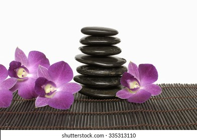 Pink orchid and stacked stones on bamboo mat texture