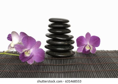 Pink orchid with stacked stones on mat