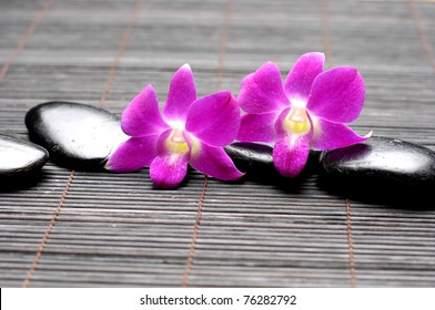 Pink orchid and zen Stones on bamboo mat