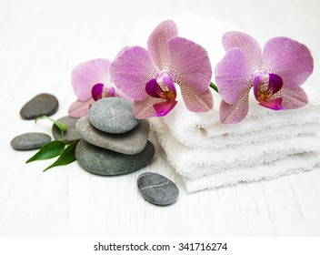 pink orchids, towels  and massage stones on a wooden background