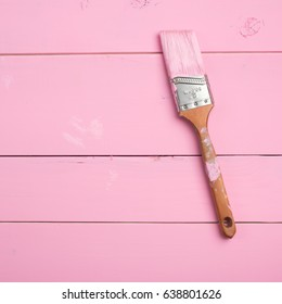 Pink Paint Brush on Bright Pink Painted, Shiplap Boards in Square Crop with Room or Space on the Side for Copy, text, or your words or design.  It's a close up photo in a flat lay, above view design.