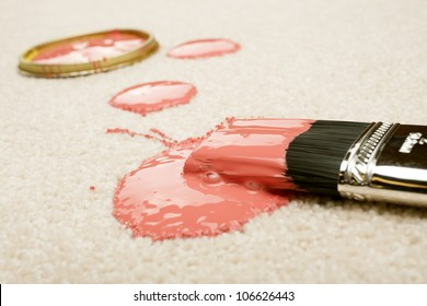 Pink paint spilled on cream coloured carpet with brush.
