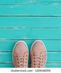 pink pair of female leather sneakers with laces on a blue wooden background
