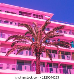 pink palm trees  and hotel against the sky. bright neon colors. minimal and surreal. summer holidays. urban style. 80s style