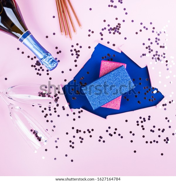 Pink paper design background with classic blue color hole and glitter gift box stack, champagne bottle, flutes and candles. Trendy festive backdrop for birthday, anniversary concept party. Square