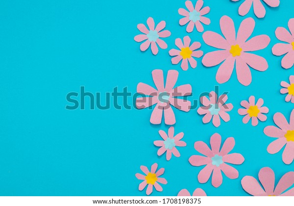 Pink paper flowers on a bright blue background. Room for copy.