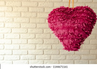 Pink paper heart pinata wait for  party