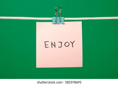 Pink paper note on clothesline with text Enjoy over colorful background