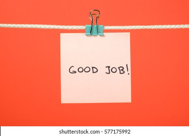 Pink paper sheet on the string with text Good Job over colorful background
