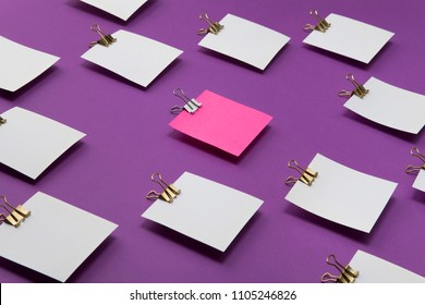 Pink paper standing out from crowd of plenty identical white papers. Think different, Leadership, uniqueness, initiative, strategy, teamwork business success concept.