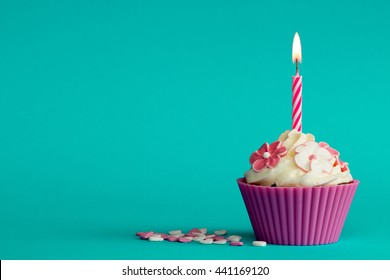 pink party cupcake with green background and burning candle