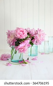 Pink peonies in glass jars on table