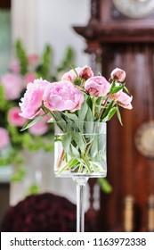 Pink peonies in glass vase. Romantic wedding decoration.
