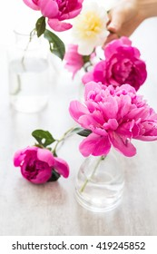 pink peonies in a glass of water.